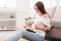 Задумчивое чтение девушки и выпивая coffe на поле стоковая фотография