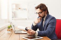 Задумчивое repor чтения бизнесмена в офисе Стоковые Изображения RF