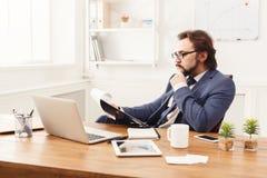 Задумчивое repor чтения бизнесмена в офисе Стоковое Изображение RF