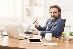 Задумчивое repor чтения бизнесмена в офисе Стоковая Фотография