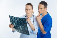 Задумчивые медицинские профессионалы думая над mri просматривают изображение стоковые фотографии rf