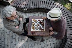 Задумчивые старшие люди играя шахмат в парке стоковые фотографии rf