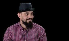 Задумчивый бородатый мужчина одел в представлять рубашки и шляпы ватки стоковое фото rf