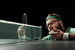 задумчивый бородатый теннисист смотря ракетку в руке стоковое фото rf