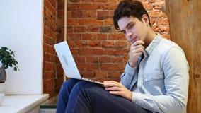 Задумчивый думая человек работая на компьтер-книжке, сидя на лестницах стоковая фотография