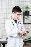 Задумчивый красивый молодой мужской доктор используя планшет Технологии в концепции медицины стоковая фотография rf