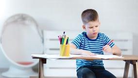 Задумчивый мальчик маленького ребенка сконцентрировал сочинительство на бумаге используя красочный карандаш на белом современном  видеоматериал