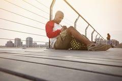 Задумчивый молодой Афро-американский человек битника ослабляя на пляже и делая примечания текста в бумажной тетради Город на стоковая фотография rf