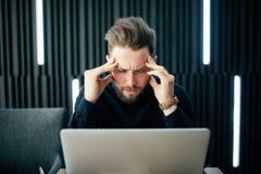 Задумчивый молодой бородатый думать и потревоженный человек сидя на офисе и работая на компьтер-книжке Кавказская мужская работа  Стоковые Фото