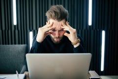 Задумчивый молодой бородатый думать и потревоженный человек сидя на офисе и работая на компьтер-книжке Кавказская мужская работа  Стоковая Фотография