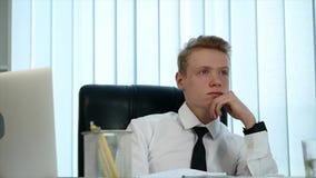 Задумчивый молодой человек сидя в его офисе на работе видеоматериал