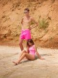 Задумчивый стоящие человек и женщина сидя на пляже Романтичные пары на заходе солнца, на золотом пляже Стоковое Изображение