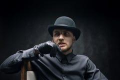 Задумчивый человек в шляпе и зубочистка в его рте, против темной предпосылки стоковые фотографии rf