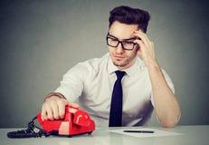 Задумчивый человек подготавливая для звонка стоковое фото