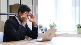 Задумчивый чернокожий человек думая и работая на компьтер-книжке Стоковое фото RF