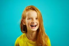 Задушевный хохот девушки детей с красными волосами на изолированной сини Счастливый ребенок выражает задушевную эмоцию стоковые фотографии rf