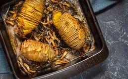 Зажаренная в духовке картошка hasselback на лотке литого железа Темная предпосылка стоковое изображение