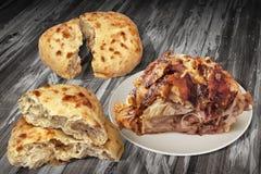 Зажаренная в духовке вертелом сочная ветчина свинины с 2 хлебцами Pitta сорванными хлебом в комплекте половины на старой треснуто Стоковое Изображение RF