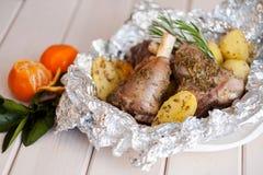 Зажаренная в духовке нога овечки с розмариновым маслом, специями, картошками Стоковое Изображение RF