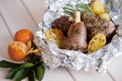 Зажаренная в духовке нога овечки с розмариновым маслом, специями, картошками Стоковая Фотография