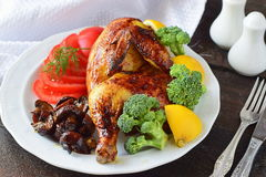 Зажаренная в духовке половина цыпленк цыпленка с кипеть брокколи, отрезанным томатом, лимоном и зажаренными грибами на белой плит Стоковая Фотография RF