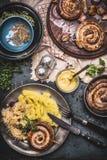 Зажаренная в духовке сосиска с картофельными пюре и замаринованной капустой служила на темной деревенской таблице с мустардом, вз Стоковое Изображение