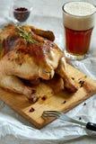 Зажаренная в духовке утка на деревянной разделочной доске и стекло пива внутри Стоковое Изображение RF