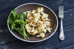 Зажаренная в духовке цветная капуста и свежий зеленый салат на коричневой плите Стоковое Изображение