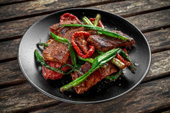 Зажаренная говядина с овощами, лук весны, спаржа на плите Стоковое Фото