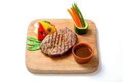 Зажаренная еда - стейк говядины BBQ с горячим соусом и овощами на деревянной доске Стоковое Фото