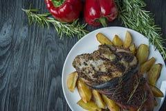 Зажаренная костяшка свинины с картошками служила на белой плите Украсил со свежим болгарским перцем, розмариновым маслом r стоковое изображение rf