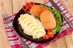 2 зажаренная обвалянная в сухарях котлета с картофельными пюре и салатом на предпосылке черной плиты деревянной Стоковая Фотография