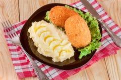 2 зажаренная обвалянная в сухарях котлета с картофельными пюре и салатом на предпосылке черной плиты деревянной Стоковое Фото