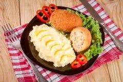 2 зажаренная обвалянная в сухарях котлета с картофельными пюре и салатом на предпосылке черной плиты деревянной Стоковые Изображения
