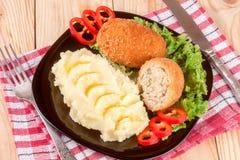 2 зажаренная обвалянная в сухарях котлета с картофельными пюре и салатом на предпосылке черной плиты деревянной Стоковые Фотографии RF