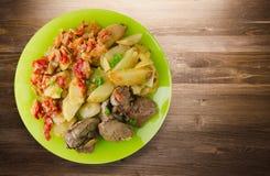 Зажаренная печень с картошками и потушенными томатами Стоковое Изображение