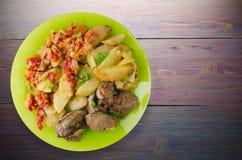 Зажаренная печень с картошками и потушенными томатами Стоковое Фото