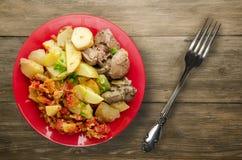 Зажаренная печень с картошками и потушенными томатами Стоковая Фотография