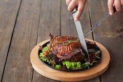 Зажаренное вырезывание бедренной кости утки с столовым прибором на древесине Стоковая Фотография