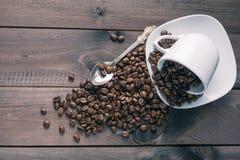 Зажаренное в духовке кофейное зерно в чашке на деревянной предпосылке Стоковая Фотография