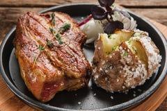 Зажаренное в духовке мясо служило на черной плите с картошкой Стоковое Изображение