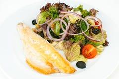 Зажаренное в духовке филе рыб с зеленым салатом Стоковая Фотография RF