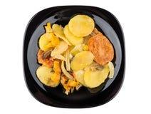 Зажаренное в духовке vegetable смешивание в черной плите изолированной на белизне Стоковые Фото