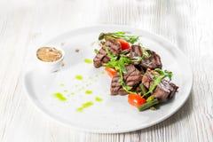 Зажаренное мясо говядины стейка очень вкусное на белой плите на светлом меню предпосылки Стоковая Фотография