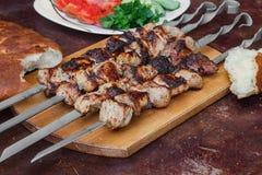 Зажаренное мясо на протыкальниках на деревянных подносе, хлебе, овощах и травах вокруг, на таблице стоковая фотография rf