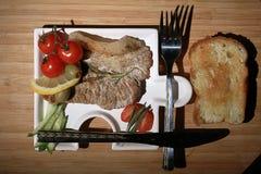 Зажаренное мясо на плите служа деревенский деревянный стол Стоковая Фотография