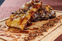 Зажаренное филе стейка мяса свинины на деревянной плите вырезывания над деревянным столом Стоковая Фотография