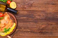 Зажаренное филе рыб с томатами на деревянном столе Стоковое Изображение RF