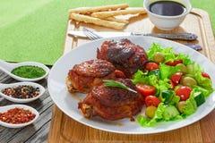 Зажаренные бедренные кости цыпленка с зеленым свежим салатом на белом диске Стоковая Фотография