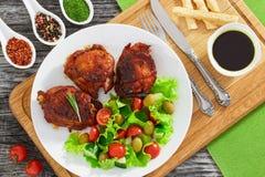 Зажаренные бедренные кости цыпленка с зеленым свежим салатом на белом диске Стоковое Изображение